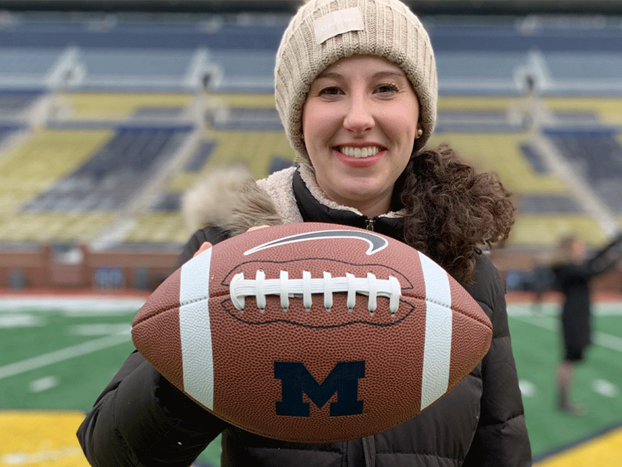 Marissa holds up a football during the field experience at Crisis Challenge